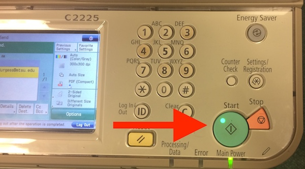 Arrow points toward the large green scan button on the scanner